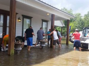 Setting up sandbags to save a house.